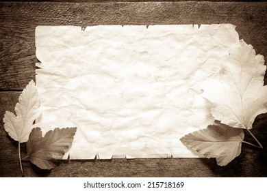 Old paper and autumn leaves over wooden surface
