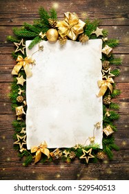 Old paper border with Christmas decorations on wooden background