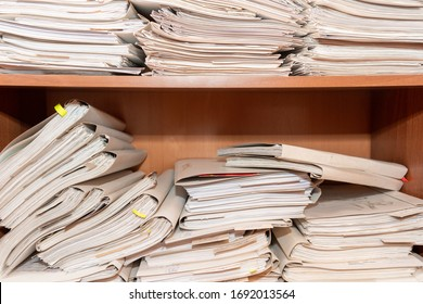 Old paper documents stacked in archive. Documents on the shelves of archive room. Office shelves in the closet full of files