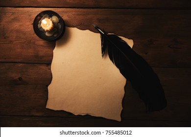 old paper and quill pen in candlelight. top view