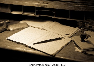 Old papers with pen on a wooden desk - sepia style