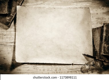 old parchment with books,spectacles and pen on antique writing desk,sepia image