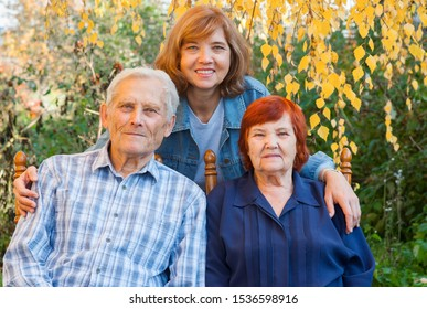 Old parents and adult daughter in  autumn garden. Happy family, adult children, care for old parents. Love and respect for elders. Good parenting