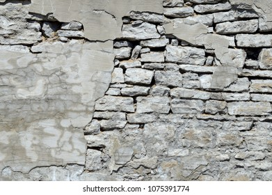 An old parged wall that has the dry cement falling apart giving a nice background texture for a graphic image.