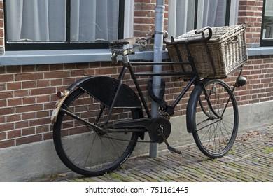 Old parked black Dutch men's bike with wicker basket
