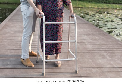 old patient and care giver relax in garden, old patient use cane to walking on the bridge, walk training, rehabilitation process,  mother's day