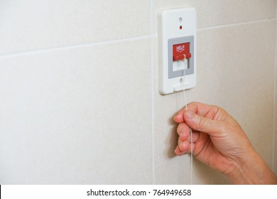 Old patient pulling a red switch calling for emergency help in the toilet