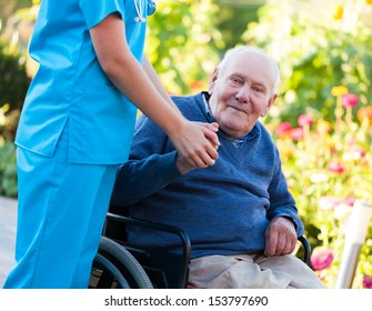 Old patient sitting in wheelchair, holding the doctor's hand.