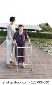 old patient use walker, old Asian female learning to use walker with care giver, walk training, family time, mother's day