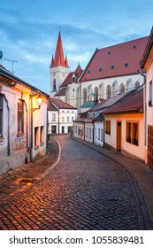 Old paved street in the historical downtown on a winter evening. View of the St. Nicholas Church. Znojmo, Czech Republic, South Moravia, Europe
