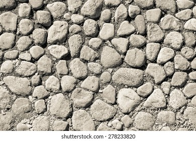 old pavement from a natural stone of beige color for the textured abstract background