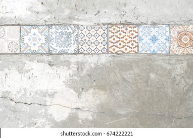 old paving tiles pattern on the concrete or cement wall with cracks. Ceramic tile pattern elegant vintage and Tuscany flowers. Tuscany or Italian style wallpaper/background.