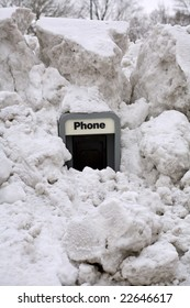 An old pay phone with piles of snow around it.