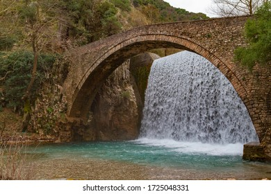 An old pedestrial bidge made by stone with a water fall behind it. The river cross a canyon, in Palaiokaria Trikala Greece.  It is a winter morning. A photo with slow shutter speed in diagonal view