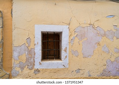 Old peeling facade with a small window