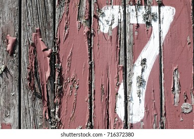 An old peeling painted wood panel wall with number seven painted on.