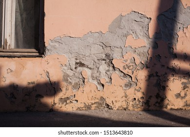 Old peeling pink facade, with accidental shape of a running horse