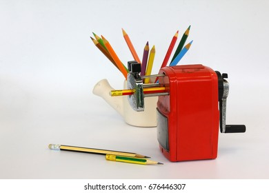 Old pencil sharpener and colored pencils on white background.