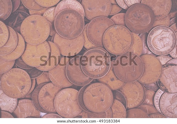 Old penny coins spread out for a background Vintage Retro Filter.