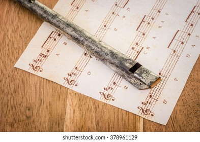 An old Penny Whistle and sheet music on an oak desk.