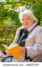 old pensioner reading a book in the park