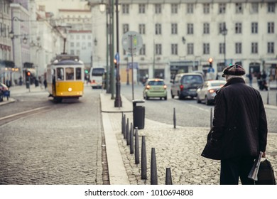 Old pensioner waiting the chance to cross the street.Senior citizen awaits public transportation the station.Elderly man in urban environment .Old age and vitality concept.Old resident in traffic