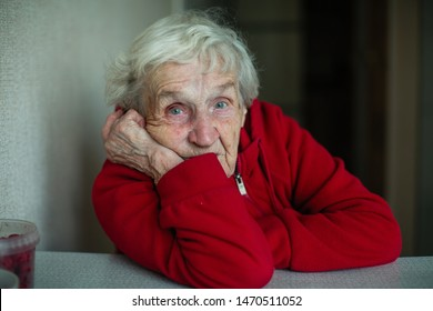 An old pensioner woman in her house, closeup portrait sitting at a table in a red jacket.
