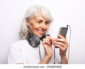 Old people, emotion and technology concept: Charming elderly woman with gray hair choosing music on smartphone over white background