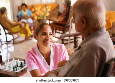 Old people in geriatric hospice: young attractive hispanic woman working as nurse takes care of a senior man on wheelchair. She talks with him then goes away to help other patients