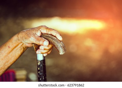 Old people or graybeard hand holding walking stick,vintage style (soft focus)