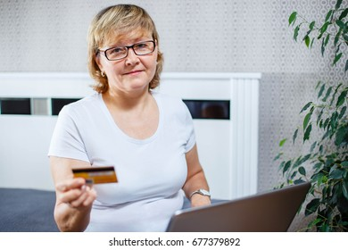 Old people and modern technology concept. Portrait of a 50s mature woman hand holding credit card, using online internet payment at home. Indoor senior people living lifestyle.