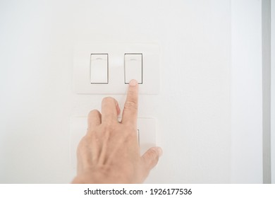 old people's hand  press electric switch on grunge white wall , close up