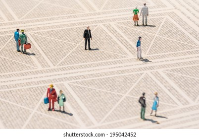 Old person miniature - Lonely man standing lost in the middle of a generic square with normal people around - Concept of solitude and elderly