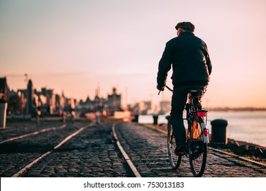 Old person riding a bicycle in Antwerp, Belgium during sunset.