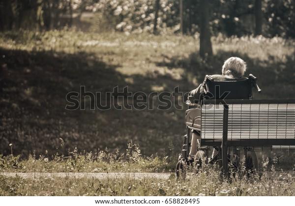 vieille personne assise au parc, image du ton de tristesse