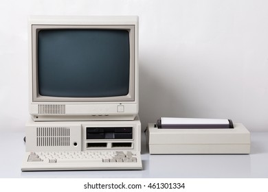 Old personal computer. The system unit, floppy drive, CRT monitor, printer and keyboard on white background.