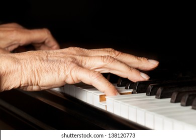 Old person's hands playing the piano. Close up view of skin texture and piano keys.