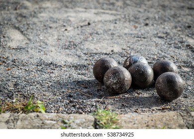Old petanque balls on the ground.