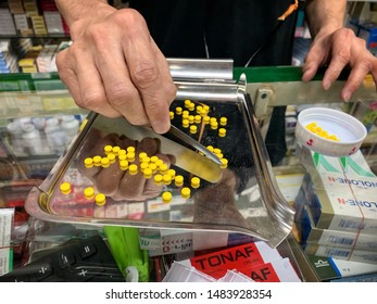 The old pharmacist's hand is counting tablets to divide the sale into small bags, Bangkok Thailand, August 2019.