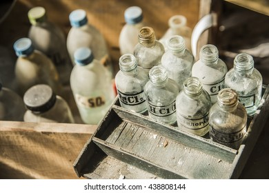 old pharmacy bottles covered with dust in pharmaceutical laboratory in wooden old box. ZnSO4, MgCl2, acid and a metal salt.