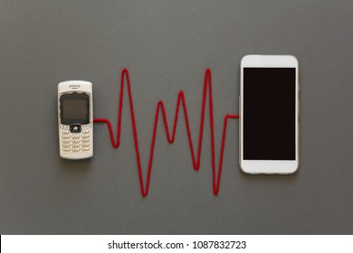Old phone and new smartphone connected by red pulse laying on grey paper background. Upgrade phone technology or generation connection concept. Flat lay. Top view