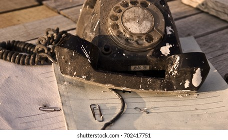 Old phone is on the table near the documents close-up