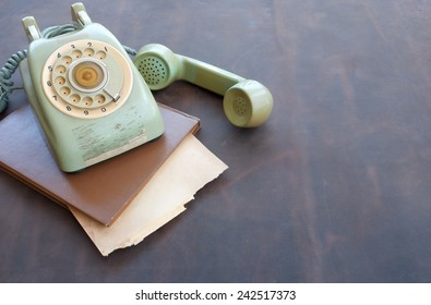 Old phone and old paper on leather background.