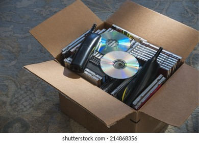 old phones and obsolete CDs in carton