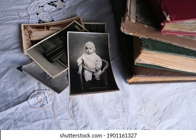 old photo albums lie on a white mint tablecloth, vintage photographs of 1960, concept of family tree, genealogy, childhood memories, connection with ancestors