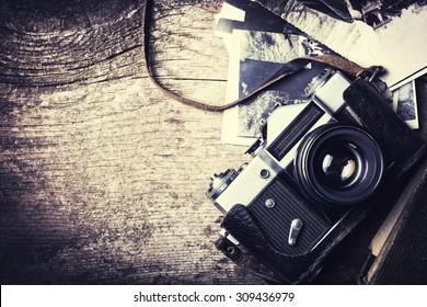 Old photo camera on vintage wooden background .