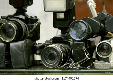 old photo equipment is dusty and not in demand. SLR cameras and flashes