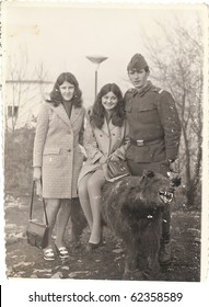 Old photo, young soldier posing with two girls