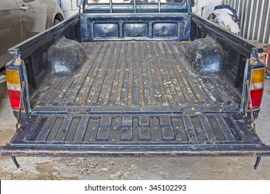 Old Pickup truck - The tailgate of a blue battered eighties Pickup Truck in rear.