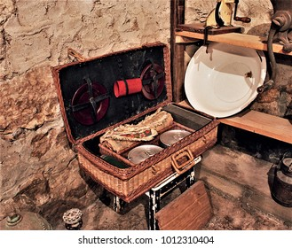 old picnic basket with crockery, in the kitchen of a rural house in Galicia, old wooden furniture, old food storage containers, typical rural cuisine of Galicia, Galician ethnographic museum,